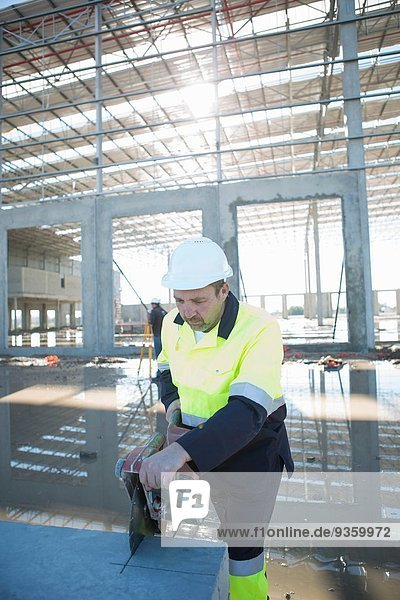 Bauherr mit rotierender Säge auf der Baustelle