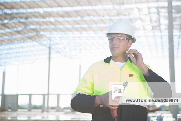Bauherr mit Elektrobohrer zum Einsetzen von Gehörschutzstöpseln auf der Baustelle