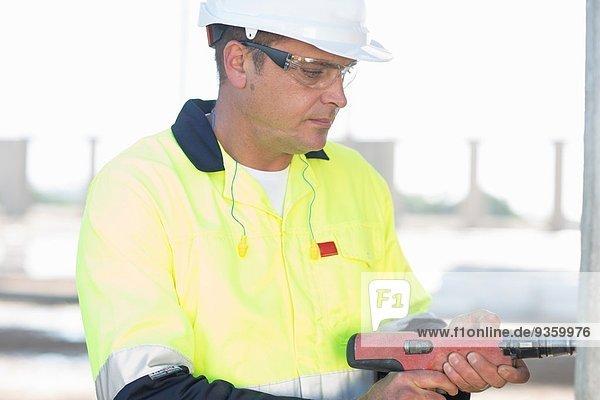 Bauherr mit Elektrobohrer auf der Baustelle