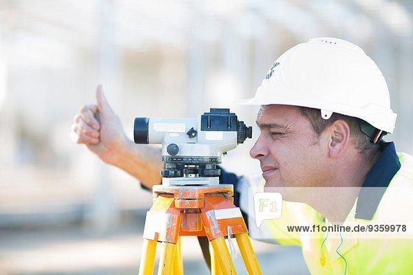 Vermessungsingenieur beim Durchblick auf der Baustelle