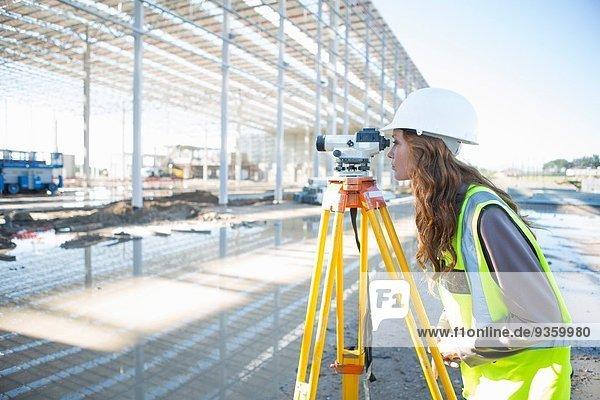 Vermessungsingenieur lehnt sich nach vorne  um auf der Baustelle durch die Ebene zu blicken.