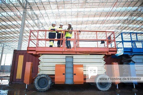 Flachwinkelansicht von Bauleiter und Architekt auf Aussichtsplattform auf der Baustelle