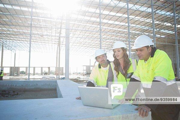 Bauleiter und Architekt mit Blick auf den Laptop auf der Baustelle