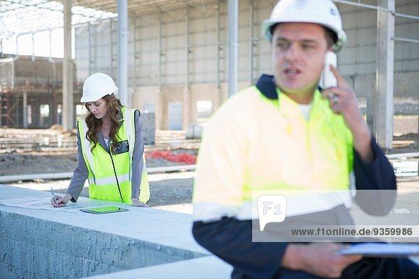 Baustellenleiter chatten auf dem Smartphone auf der Baustelle
