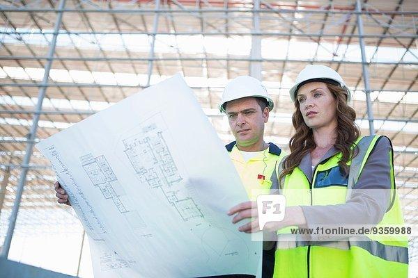Bauleiter und Architekt mit Blick auf den Bauplan auf der Baustelle