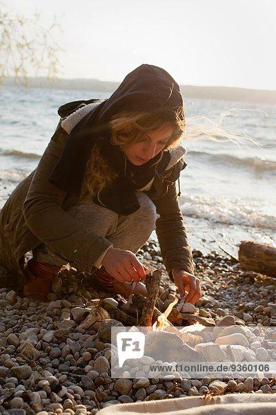 Frau macht ein Feuer am Meer