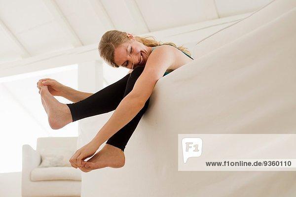 Woman dangling legs over sofa