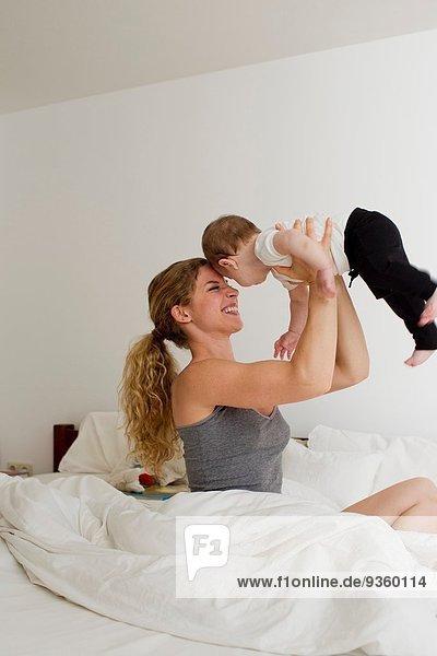 Mutter hält den kleinen Jungen in der Luft.