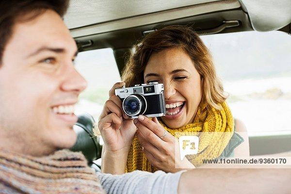 Junge Frau fotografiert Freund während der Fahrt  Kapstadt  Western Cape  Südafrika