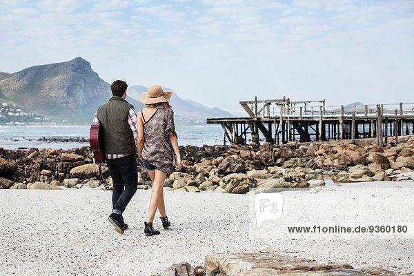 Junges Paar beim Strandspaziergang mit Gitarre  Kapstadt  Westkap  Südafrika
