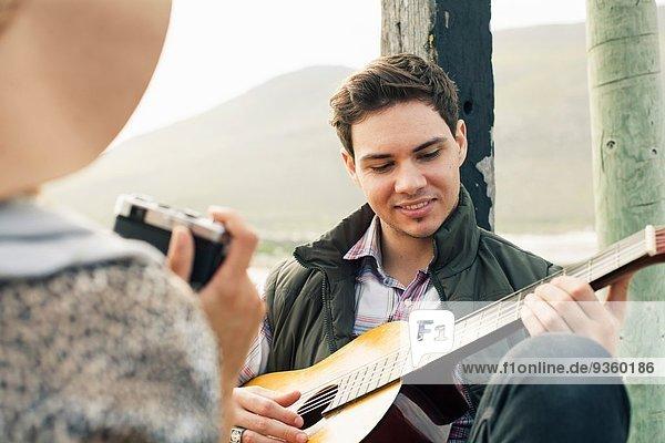 Junger Mann spielt Akustikgitarre für Freundin am Küstenpier  Kapstadt  Westkap  Südafrika