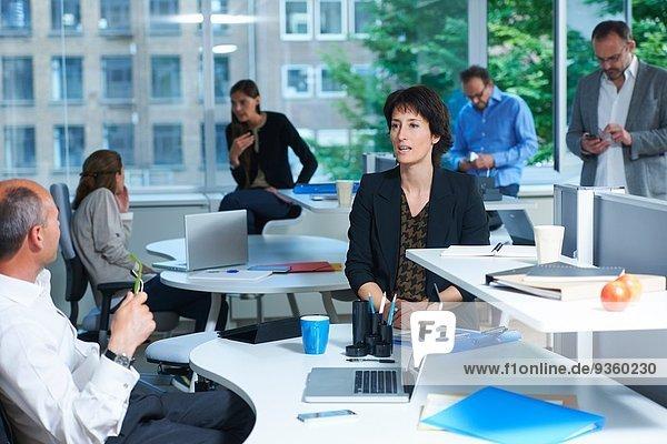 Sechs Geschäftskollegen  die in einem geschäftigen Büro arbeiten