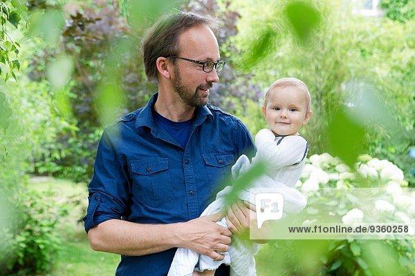 Vater mit Tochter im Garten