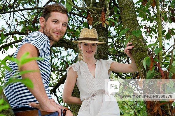 Porträt des mittleren erwachsenen Paares neben dem Gartenbaum