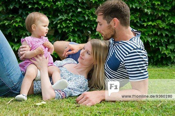 Mittleres erwachsenes Paar mit kleiner Tochter auf Rasen im Garten liegend