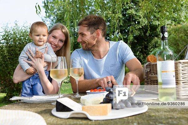 Mittleres erwachsenes Paar und kleine Tochter am Picknicktisch im Garten sitzend