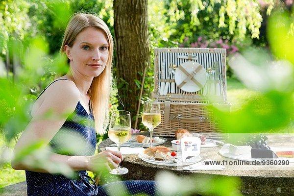 Porträt einer mittleren erwachsenen Frau am Picknicktisch mit einem Glas Weißwein im Garten