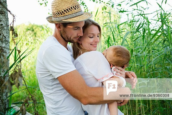 Mittleres erwachsenes Paar und kleine Tochter mit Armen umeinander in Schilfrohr