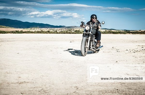 Reifer Mann auf dem Motorrad durch die trockene Ebene  Cagliari  Sardinien  Italien