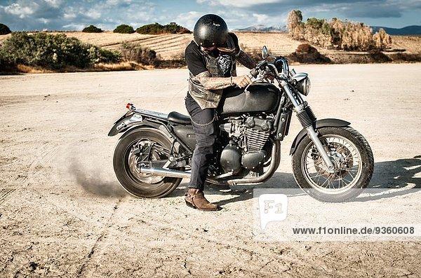 Erwachsener Mann spinnt Motorradrad auf trockener Ebene  Cagliari  Sardinien  Italien
