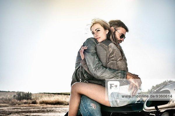 Junges Paar umarmt und spreizt Motorrad auf trockener Ebene  Cagliari  Sardinien  Italien