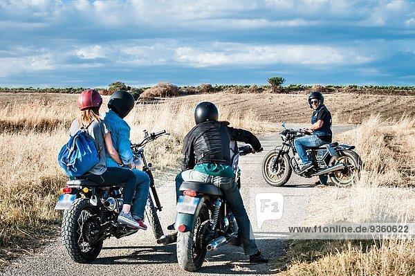 Rückansicht von vier Freunden  die sich auf Motorrädern auf der Landstraße unterhalten  Cagliari  Sardinien  Italien
