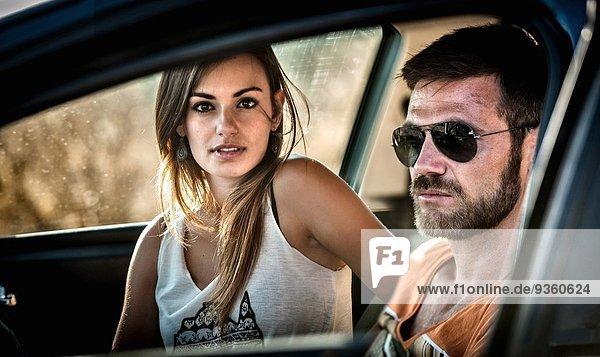 Nahaufnahme des jungen Paares durch das Autofenster