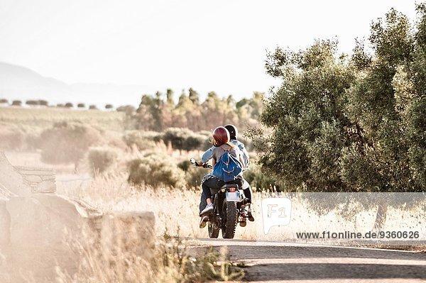 Rückansicht des mittleren erwachsenen Paares auf staubiger Landstraße  Cagliari  Sardinien  Italien