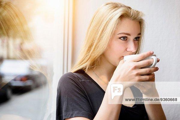 Junge Frau trinkt Kaffee im Fenstersitz