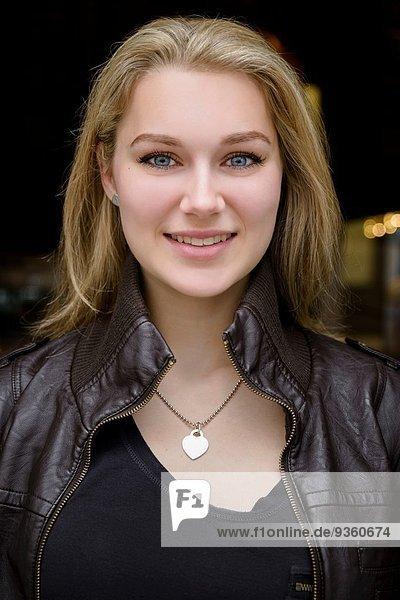 Porträt einer selbstbewussten jungen Frau vor dem Café
