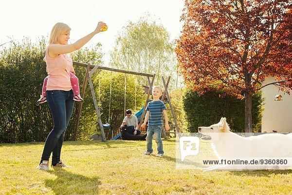 Family in garden training dog