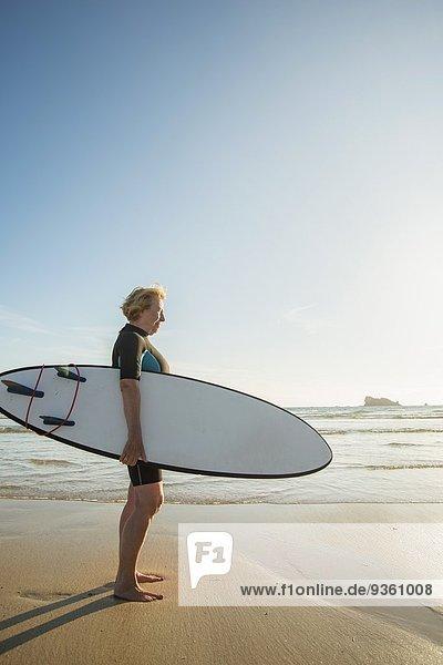 Seniorin am Strand stehend mit Surfbrett  Camaret-sur-mer  Bretagne  Frankreich