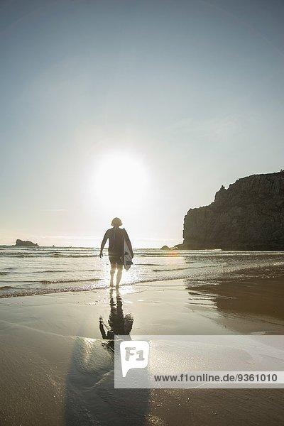 Seniorin auf dem Weg zum Meer mit Surfbrett,  Camaret-sur-mer,  Bretagne,  Frankreich