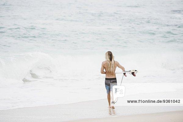 Australischer Surfer mit Surfbrett am Strand