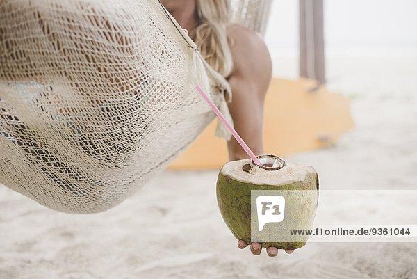 Mann genießt Kokoswasser in der Hängematte am Strand