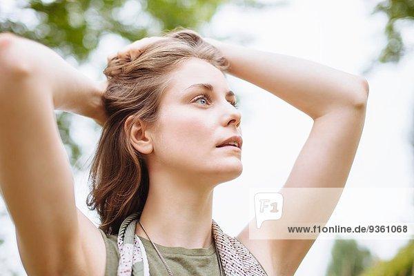 Gelassene junge Frau  die mit den Händen in den Haaren aufblickt.