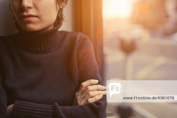 Porträt einer jungen Frau mit gefalteten Armen neben dem Fenster