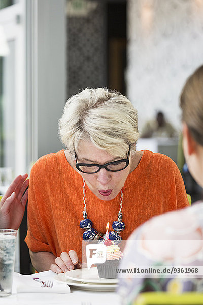 Woman celebrating birthday in restaurant