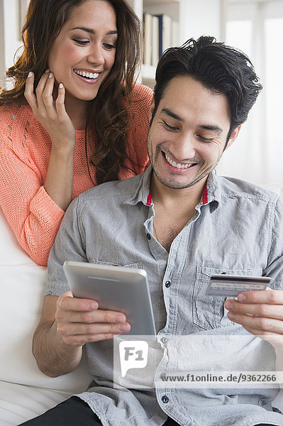 Couple shopping together on tablet computer