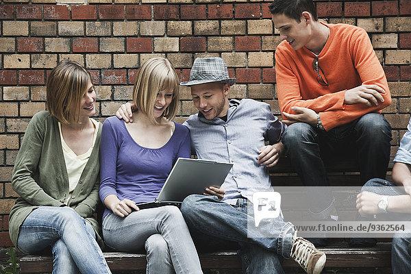 Deutschland  Berlin  Mann und Frau sitzend mit Laptop auf Bank