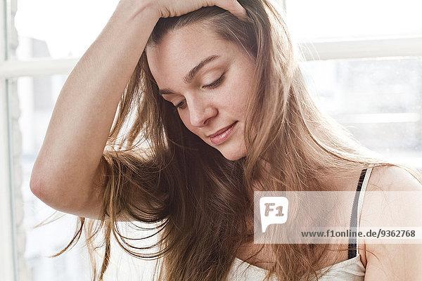 Porträt der lächelnden jungen Frau mit der Hand im Haar