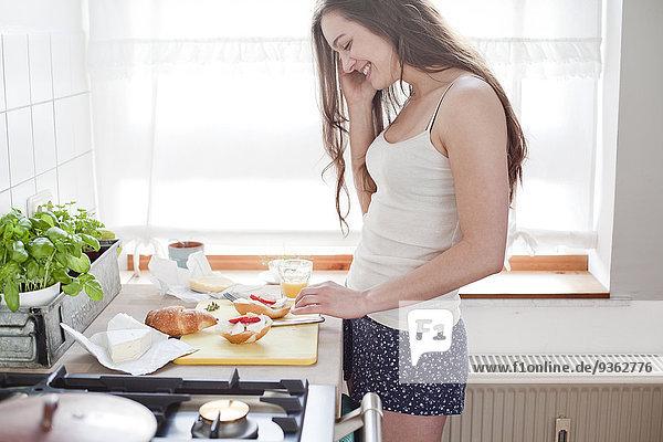 Porträt einer lächelnden jungen Frau  die in ihrer Küche telefoniert.
