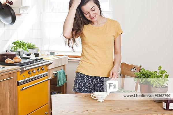 Junge Frau steht in ihrer Küche