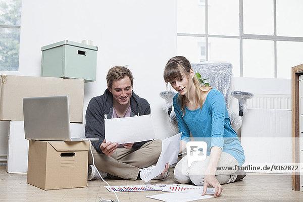 Zwei Kollegen sitzen auf dem Boden zwischen Pappkartons in einem Büro.