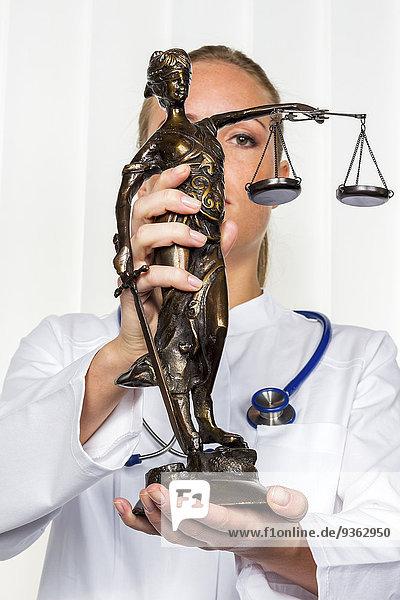 Ärztin mit Lady Justice Figur