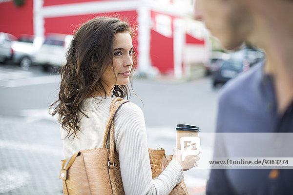 Porträt einer Frau mit Kaffee zum Mitnehmen