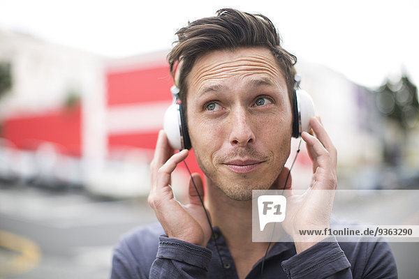 Portrait of young man listening music with headphones
