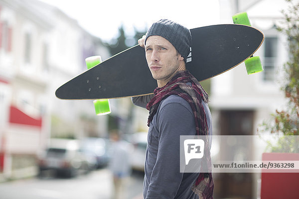 Portrait of young man holding skateboard on his shoulder