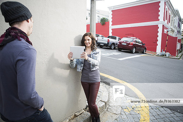 Young woman taking a picture of her boyfriend with digital tablet