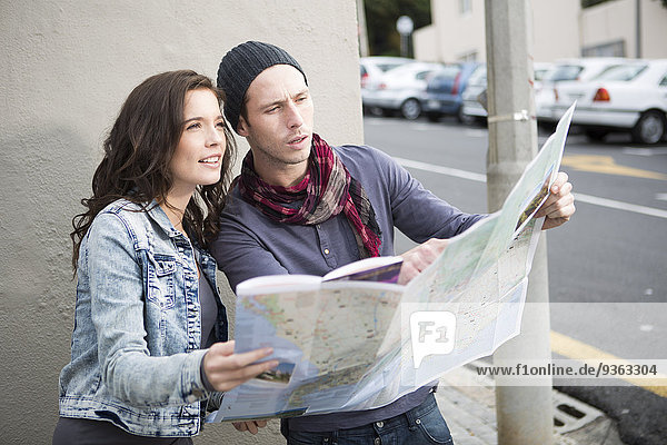 Young couple orientating with city map